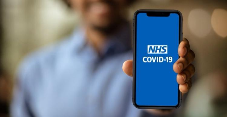 Man holding phone displaying Covid-19 app