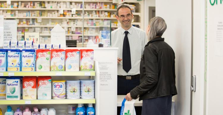 Woman at counter of a pharmacy talking to a pharmacist