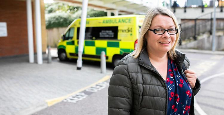 Woman smiling at the camera outside in a hospital car park