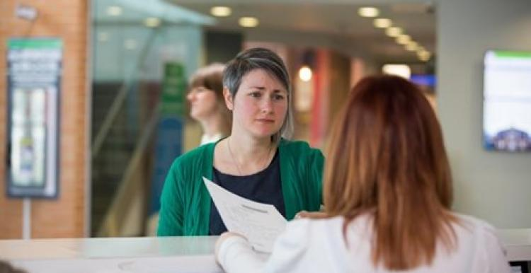 Young woman talking to another woman working on reception in a health care setting