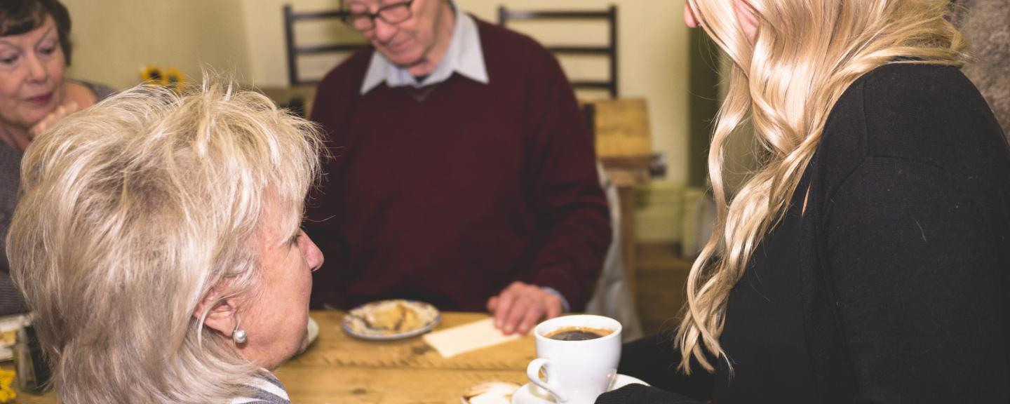 Group of older people sitting around a table in a cafe being served drinks and food