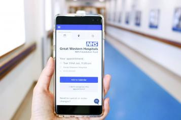 Picture of a hand holding a phone showing Great Western Hospital online booking tool