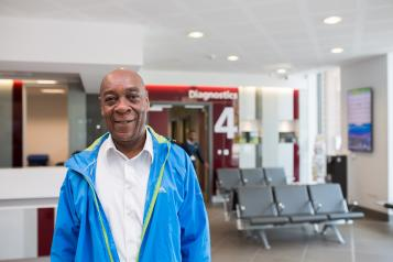 Older man standing in a hospital with a large diagnostics sign behind him