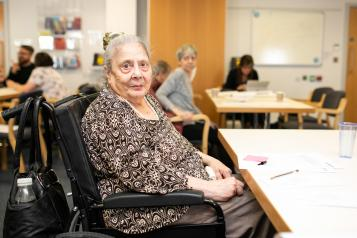 Photo of an elderly woman in a wheelchair looking directly at the camera