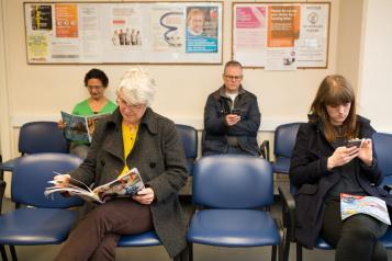 GP surgery reception with people waiting to be seen