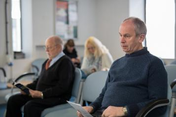 Photo of a middle aged man with people in the background all sitting in a waiting room in a medical setting