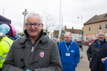 Older man standing outside with a coat on smiling directly at the camera