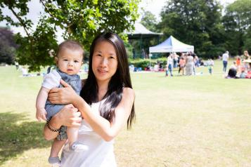 Mother holding her baby at an outdoor summer event