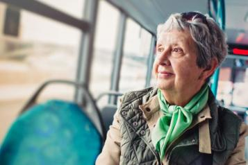 Elderly woman sitting on a bus looking out the window