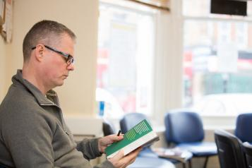 Middle aged man sitting in empty reception area of a GP reading a leaflet