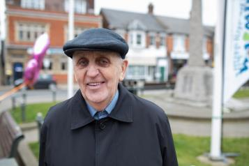 Elderly man standing outside smiling at the camera