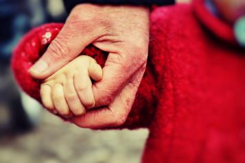 close up of toddler's hand being held by an adult