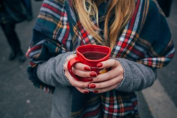 Woman holding a heart shaped mug with coffee standing outside