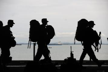 3 soldiers walking in a line with their backpack and weapons in front of a large body of water such as a lake