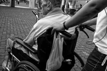 A black and white photo of an older man in a wheelchair being pushed by someone