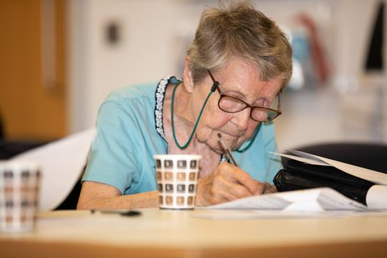 Older woman sitting at a table writing