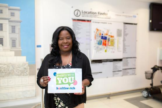 woman in hospital setting smiling at the camera holding a sign which says 'It Starts with you'