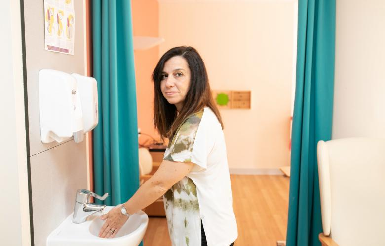 Woman in hospital setting looking at the camera whilst washing her hands
