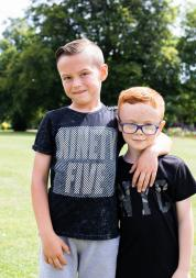 Two young boys, possibly brothers, standing together in a park outside in the summer