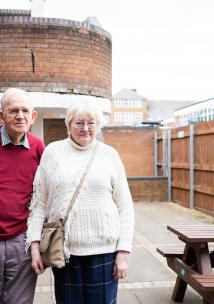 Elderley couple standing outside a building together