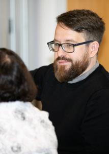 Man talking to a woman at a meeting.